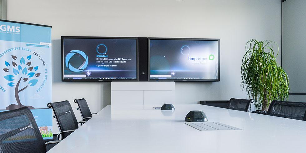 Showroom bei GMS mit Bildschirmen und Konferenztisch.