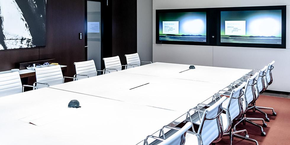 Konferenzraum mit weißem Tisch und weißen Stühlen sowie zwei Bildschirmen.
